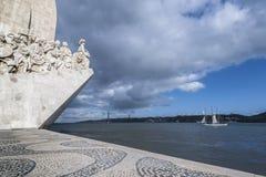 De glimp van het monument aan de ontdekkingen en overbrugt 25 April op de rivier Tagus in Lissabon royalty-vrije stock fotografie