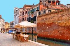 De glimp van Venetië met één van zijn kanalen met boten, de historische gebouwen en de mensen drinken en ontspannen als openlucht stock afbeeldingen