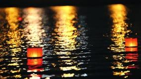 De gloeiende lantaarns op een stadsrivier bij nacht - romantisch festival stock footage