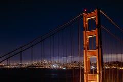 De gloeiende stad van San Francisco door Golden gate bridge Stock Afbeelding