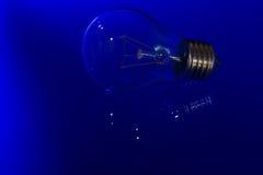 De gloeilamp met het branden van gloeidraad legt op blauwe oppervlakte met reflec Stock Afbeelding