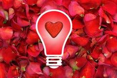 De gloeilamp met schittert hart in centrum op droge roze bloemblaadjeachtergrond Royalty-vrije Stock Foto