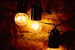 De gloeilamp van Edison het hangen op een lange draad Comfortabel warm geel licht retro Stock Afbeelding