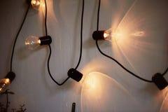 De gloeilamp van Edison het hangen op een lange draad Comfortabel warm geel licht retro Royalty-vrije Stock Foto's