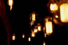 De gloeilamp van Edison het hangen op een lange draad Comfortabel warm geel licht retro Stock Afbeeldingen