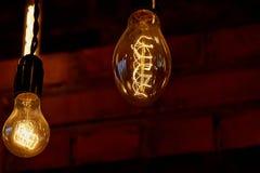 De gloeilamp van Edison het hangen op een lange draad Comfortabel warm geel licht retro Stock Foto's