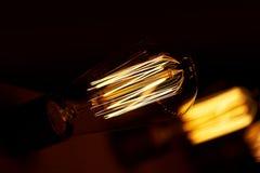 De gloeilamp van Edison het hangen op een lange draad Comfortabel warm geel licht retro Royalty-vrije Stock Afbeeldingen