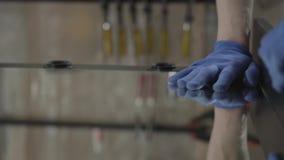De gloved hand die van de timmerman die op de spiegeloppervlakte drukken, het lijmen aan de raad, sluit omhoog Concept hand stock footage