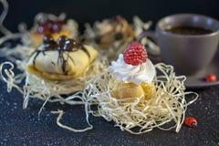 De goddelijke gebakjes met frambozen en de room, met een bodem onder de cake, vertroebelen de achtergrond met andere gebakjes en  stock foto