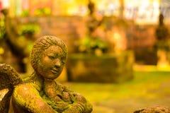 De Godin van het gipspleistergezicht Heilig met groen mos stock fotografie