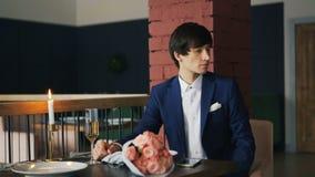 De goed-geklede boze jonge mens wacht op zijn recent meisje in restaurant, gebruikend smartphone dan weggaand modern stock video