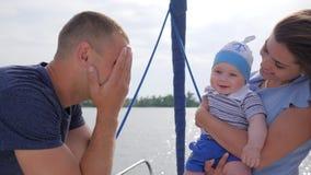 De goede stemming van vriendschappelijke familie op vakantie aan rivier, jonge mamma en papa speelde met baby op overzees in boot stock videobeelden