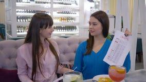 De goede voeding, het portret van gelukkige meisjes die in het plan van het handendieet houden en de calorieën maken van en kijke stock footage