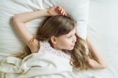 De goedemorgen, het blonde van het Kindmeisje met lang golvend haar ontwaakt Liggend op een hoofdkussen in bed, hoogste mening stock fotografie