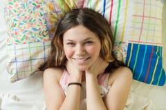 De goedemorgen, tiener ontwaakt en glimlacht bij de camera liggend op een hoofdkussen in haar bed, hoogste mening stock afbeeldingen