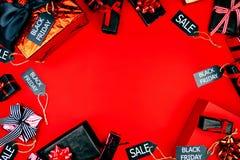 De goederen en stellen in zwarte en rode dekking met zwarte verkoopetiketten voor op rode achtergrond Verkoop en korting in winke royalty-vrije stock afbeeldingen