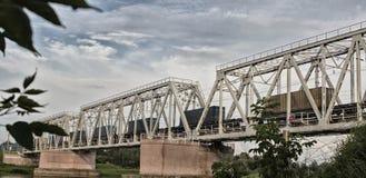 De goederentrein beweegt zich langs de spoorwegbrug over de rivier stock afbeeldingen