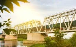 De goederentrein beweegt zich langs de spoorwegbrug over de rivier stock foto's