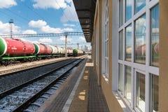 De goederentrein met tanks bevindt zich op de sporen naast de bouw van het centraal station De treintanks met olie en brandstof royalty-vrije stock fotografie