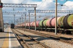 De goederentrein met tanks bevindt zich op de sporen naast de bouw van het centraal station De treintanks met olie en brandstof stock fotografie