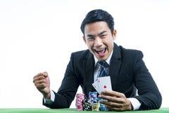 De gokker is zeer gelukkig om pookkaarten te winnen en weddenschap te ontvangen l stock foto's