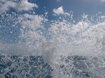 De golf explodeert in de lucht met blauwe wolkenhemel op de achtergrond royalty-vrije stock afbeeldingen
