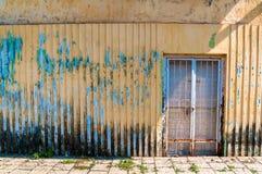 De golf gele muur met shuttered deur en afschilferende verf stock afbeelding