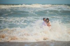 De golf veegde de jonggehuwden Bruid en bruidegom het stellen in het overzees royalty-vrije stock fotografie