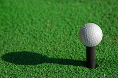 De golfbal op T-stuk en imiteert groen Royalty-vrije Stock Foto