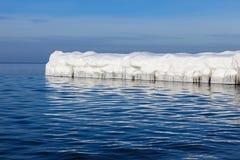 De golfbreker in de vorm van een ijsberg in een Zonnige de winterdag Stock Fotografie