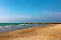 De golfbreker die zich van het strand in het overzees uitbreiden stock afbeelding