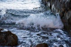 De golfbroodjes op de rotsen Overzeese branding Bevroren beweging royalty-vrije stock foto's