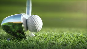 De golfclub raakt een golfbal in een super langzame motie, in zonnige ochtend stock video