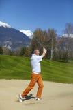 De golfspeler van de mens bij de bunker op een golfcursus Royalty-vrije Stock Afbeeldingen