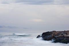 De golven die de rotsen raken royalty-vrije stock foto