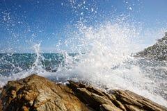 De golven die op een steenachtig strand breken Stock Foto's
