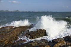 De golven die op een steenachtig strand breken, die een nevel vormen Stock Afbeelding