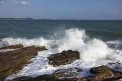 De golven die op een steenachtig strand breken, die een nevel vormen Stock Fotografie