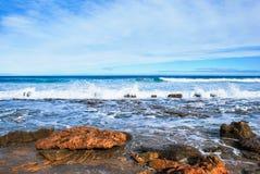 De golven die op rotsen, perfecte blauwe oceaan, rotsen bij de kust, altostratus verpletteren betrekt in de hemel, Stock Foto's