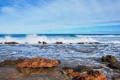 De golven die op rotsen, water verpletteren barst in de lucht, perfecte blauwe oceaan, rotsen bij de kust, altostratuswolken in d Stock Foto's