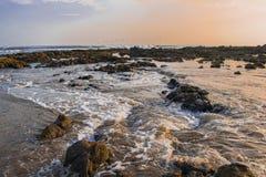 De golven die de rotsen strelen stock fotografie