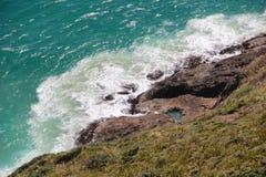 De golven die tegen de helling van de rots slaan Stock Fotografie