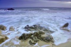 De golven en de rotsen Stock Foto's