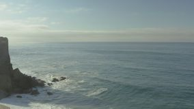 De golven en de rotsen van een klip op het strand stock videobeelden