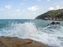 De golven slaan op de stenen met plonsen stock foto