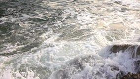 De golven slaan tegen de steenachtige kust van de overzeese vorm de nevel en het schuim Langzame Motie stock footage