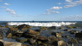 De golven slaan tegen stenen, een somber landschap Stock Afbeeldingen