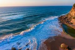 De golven van de Atlantische Oceaan op zandig strand dichtbij het kleine dorp Azenhas do Mar van Portugal royalty-vrije stock afbeelding