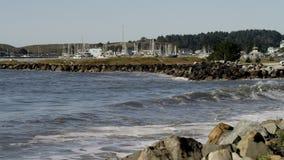 De golven van de oceaan slaan tegen de rotsachtige klippen stock video