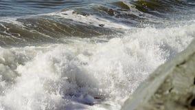 De golven van de oceaan slaan tegen de rotsachtige klippen stock videobeelden